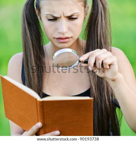 portrait serious beautiful long hair woman magnifier regards book green park background
