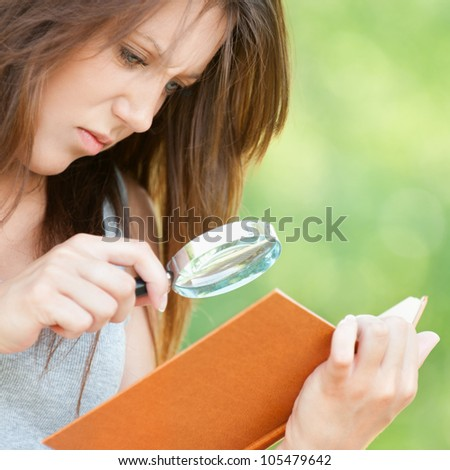 Portrait serious beautiful young woman magnifier regards book at summer green park