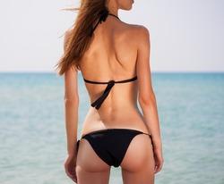 Portrait sexy beautiful back ass woman, has haired long hair, black bikini, slim tan body. Posing in tropical hot sea. Epilation
