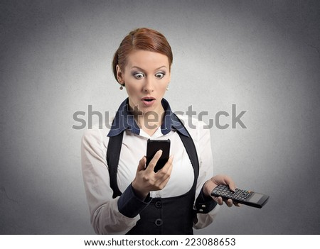 Portrait shocked businesswoman looking on smart phone holding calculator unexpected financial bills charges isolated grey wall background. Human face expression, emotion, body language, reaction