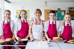 Portrait shot a home economics teacher and her students with desserts in the kitchen classroom.