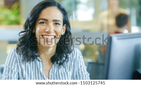 Portrait Shot of a Beautiful Young Hispanic Woman Working on a Computer, Smiling Warmly on the Camera. In the Background Busy Office with Working Colleagues. #1103125745
