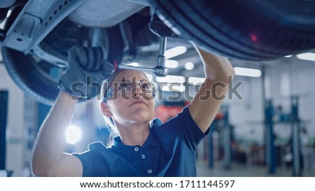 Portrait Shot of a Female Mechanic Working Under Vehicle in a Car Service. Empowering Woman Wearing Gloves and Using a Ratchet Underneath the Car. Modern Clean Workshop. Foto stock ©