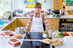 Portrait shot of a frustrated home economics teacher cooking in a kitchen classroom.