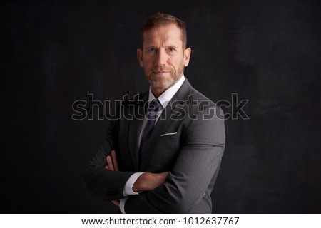 Portrait shot of a middle aged businessman wearing suit while standing with arms crossed at dark background.