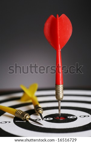 Portrait shot of a Red dart on bull's eye of a dart board