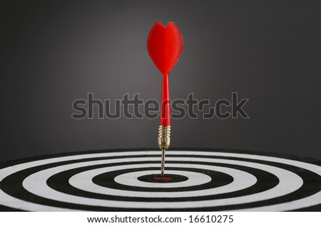 Portrait shot of a Red dart on bull's eye of a dart board