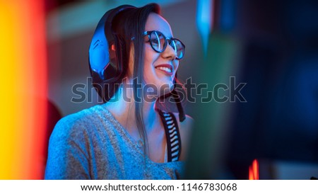Portrait Shot of a Smiling Beautiful Professional Gamer Girl Playing in First-Person Shooter Online Video Game on Her Personal Computer. Casual Cute Geek wearing Glasses and Talking into Headset.