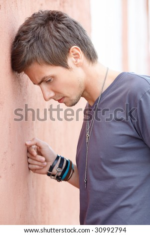 Portrait shot of a young attractive man in frustration or depression stays near the wall. Outdoor.