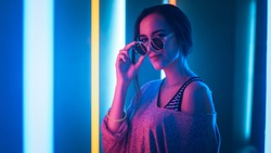 Portrait Shot of a Young Elegant Disco Girl Wearing Sunglasses. Room Lit in Retro / Retrowave Style with Neon and Pink Lights.