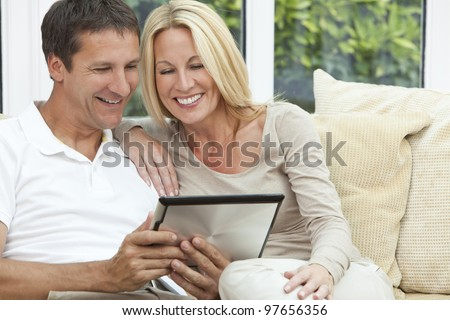 Portrait shot of an attractive, successful and happy middle aged man and woman couple in their forties, sitting together at home on a sofa using tablet computer