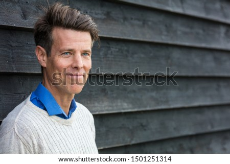 Portrait shot of an attractive, successful and happy middle aged man male outside wearing a white sweater