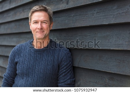 Portrait shot of an attractive, successful and happy middle aged man male smiling outside wearing a blue sweater #1075932947