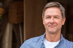 Portrait shot of an attractive, successful and happy middle aged man male wearing a blue shirt leaning on a post by a garage or barn