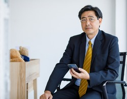 Portrait shot of Asian senior old stress businessman in formal suit and golden eyeglasses sit on chair worrying reading business text message from customer through mobile smartphone in company office.