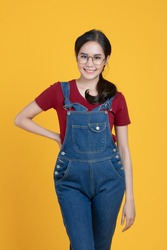 Portrait shot of beautiful Asian woman in a denim dungarees. She put her hand on hip and smile with confidence in herself isolated on yellow background.