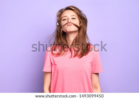 Portrait shot of cheerful funny girl having playful mood, making moustache with her hair, joking and having great time with friends at pyjamas party, lots of feathers in messy hair after pillow fight.