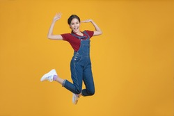 Portrait shot of happy beautiful Asian woman in denim dungarees. She jumping by proud in herself isolated on yellow background.