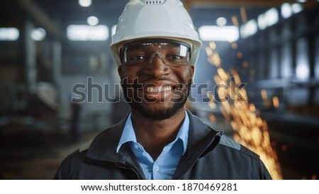 Portrait Shot of Happy Professional Heavy Industry Engineer Worker Wearing Uniform, Glasses and Hard Hat in Steel Factory and Smiling on Camera. Industrial Specialist in Metal Construction Manufacture