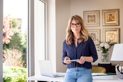 Portrait shot of middle aged woman holding digital tablet in her hand while looking at camera and smiling. Smiling businesswoman working from home. Home office.