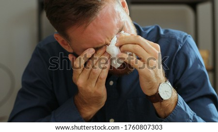 Portrait shot of sad desperate man crying during his work and usining napkins to removing tears in the office. Foto stock ©
