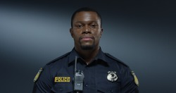 Portrait shot of the handsome young African American policeman in the uniform and walkie-talkie looking straight to the camera with serious face. Close up.