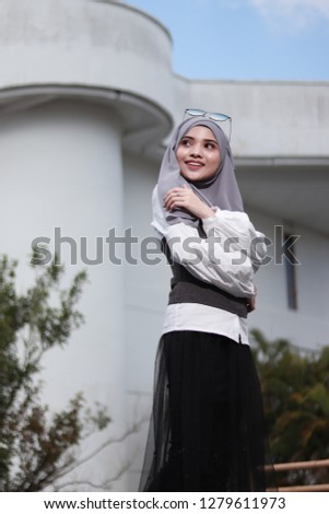 Portrait shot of women wearing hijab. Modest fashion inspiration. Women with white building background. Architectural building. #1279611973