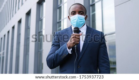 Portrait shot of young African American handsome male journalist in medical mask talking with microphone for news episode outdoor. Pandemic concept. Man correspondent in suit and tie and with mic. Foto stock ©