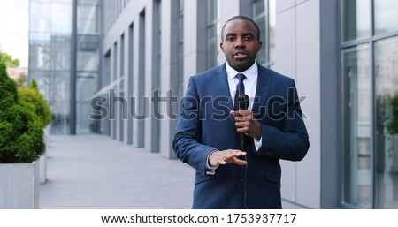 Portrait shot of young African American handsome male journalist talking with microphone for news episode outdoor. Pandemic concept. Man correspondent in suit and tie and with mic.