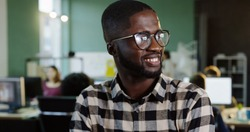 Portrait shot of young African American man in glasses turning his head to the camera and smiling in the modern office. Working people on the blurred background. Close up