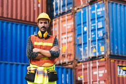 Portrait smart creative foreman engineer man wear safety helmet standing arms cross and looking camera. Logistic, transportation, import and export concept with copy space.