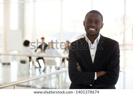 Portrait smiling African American businessman with arms crossed look at camera in company office hallway, confident employee posing for photo in modern workspace, worker in suit making picture