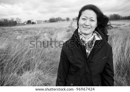 Portrait smiling asian woman looking at camera in the field
