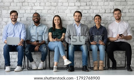 Portrait smiling diverse candidates sitting on chairs in row, looking at camera, business people applicants interns waiting for job interview, holding gadgets, employments and recruitment concept