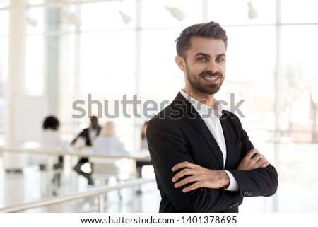 Portrait smiling employee standing with arms crossed look at camera in company office hallway, confident businessman posing for photo in modern workspace, worker in suit making picture