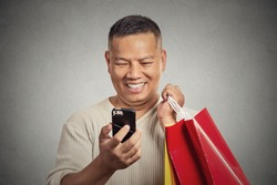 Portrait smiling handsome man holding red shopping bags looking at his smartphone isolated on grey wall background