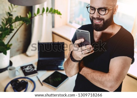 Portrait smiling handsome man reading text message, standing indoors.Businessman sends messages.Stylish brunette hipster uses mobile phone at home. Guy is chatting online. Man browsing social network. #1309718266