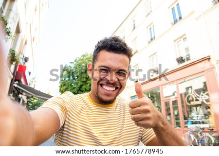 Portrait smiling young african american mixed race man taking selfie on city street ストックフォト ©