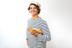 Portrait smiling young French man with beret and baguette in hand against isolated white background
