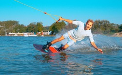PORTRAIT: Smiling young male wakesurfer riding in the waterski cable park on a sunny summer day. Cinematic shot of handsome blonde man wakeboarding on the lake and splashing the water behind him.