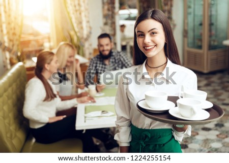 Portrait smiling young waitress standing in cafe. The happy girl the waiter holds in bunches a tray with utensils. Spacing orders to visitors of the restaurant. Restaurant service.