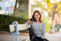 Portrait smiling young woman sitting on park bench looking at cellphone