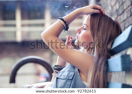 portrait smoking girl on the street in summer