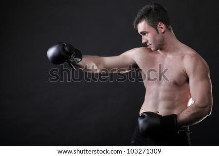 Portrait sportsman boxer in studio against dark background - stock photo