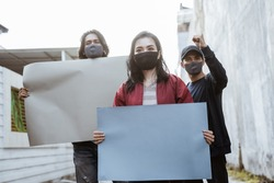 Portrait students holding blank paper conducting demonstrations by following health protocols