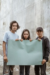 Portrait students holding blank paper who are burning with enthusiasm doing a demonstration together