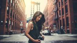Portrait style of a woman on the street in sunny day with a beautiful spot scene of New York city at summer season