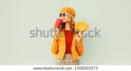 Portrait stylish happy woman drinking coffee with yellow maple leaves wearing french beret posing over gray wall background