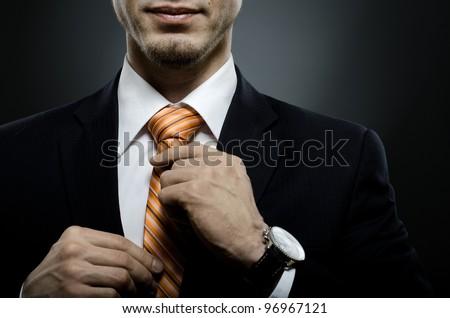 portrait  the  beautiful  businessman  in black costume tie one's necktie Stock photo ©