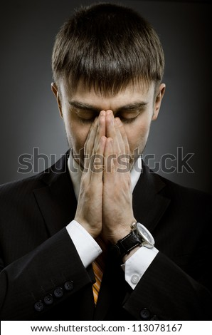 portrait  the  businessman careerist in black costume grieve and praying